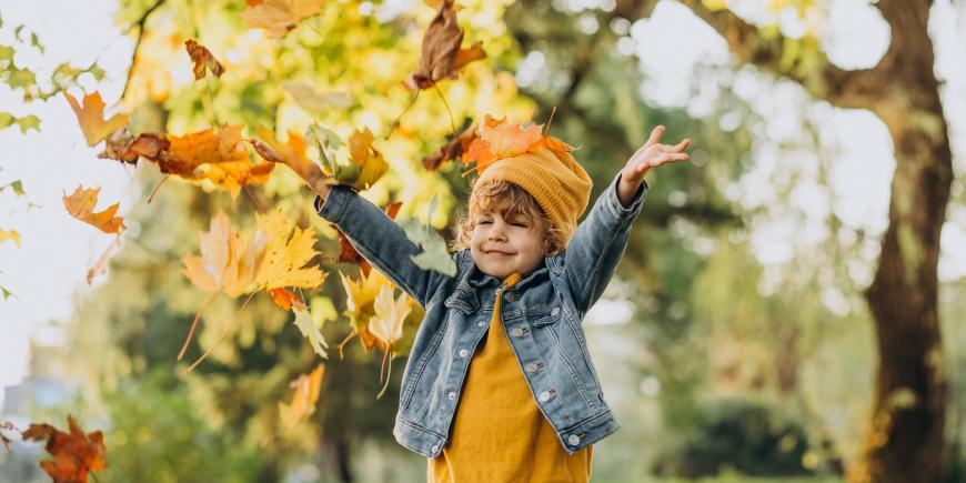 chlapec hrajúci sa s listami na jeseň v parku